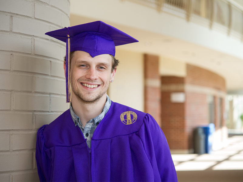 Scholarship recipient Briar Boggs posing in the Bardo Fine and Performing Arts Center decked to the nines in his purple cap and gown.