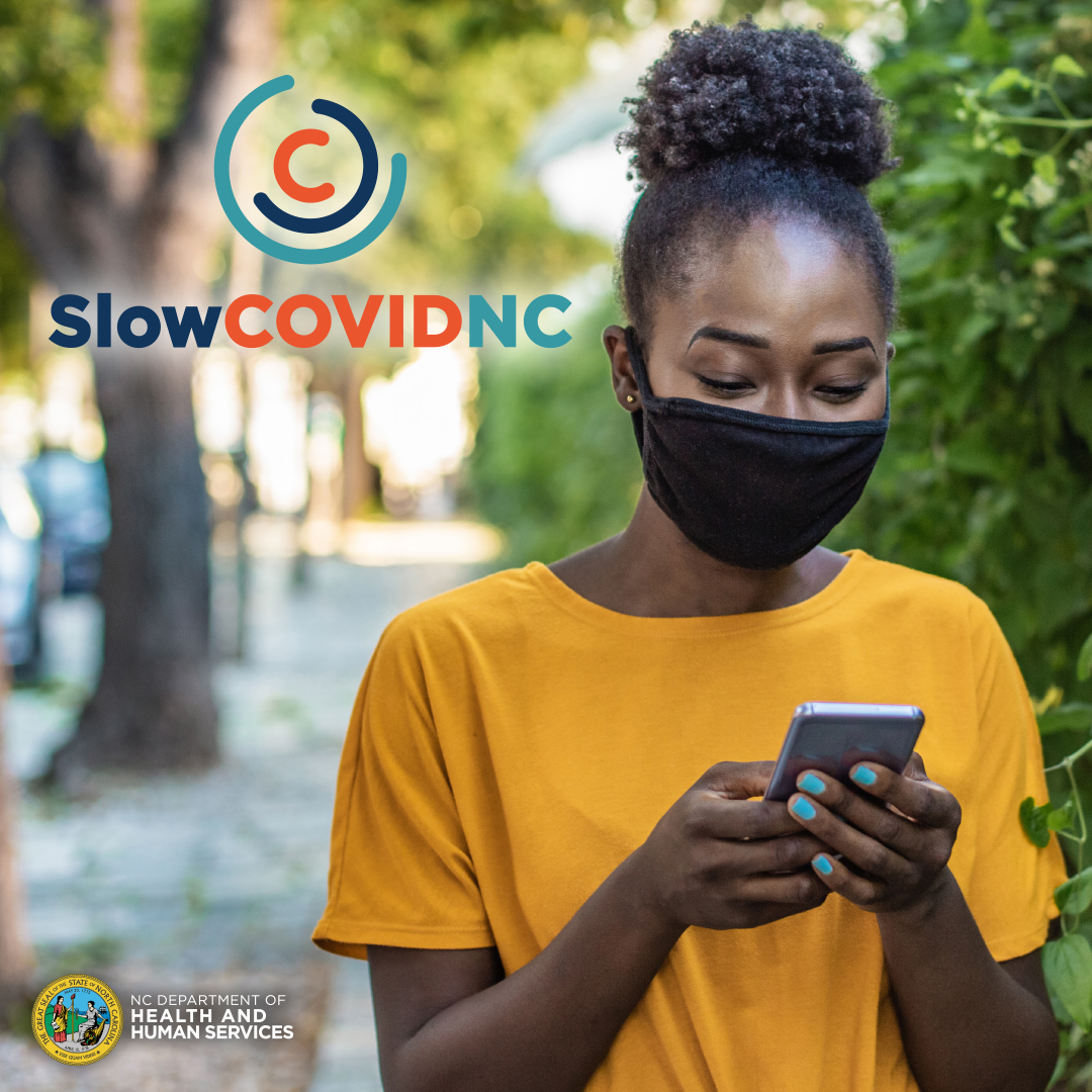 "A student wearing a mask and holding a phone with ""Slow COVID NC"""