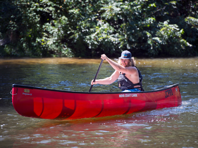 male student paddling a canoe on a river