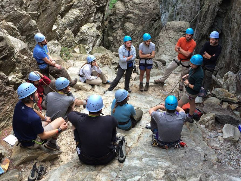 students wearing helmets sit in a circle and listen to rock climbing instructions