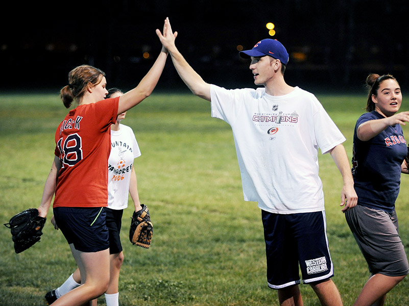 students with softball gloves high five after a game