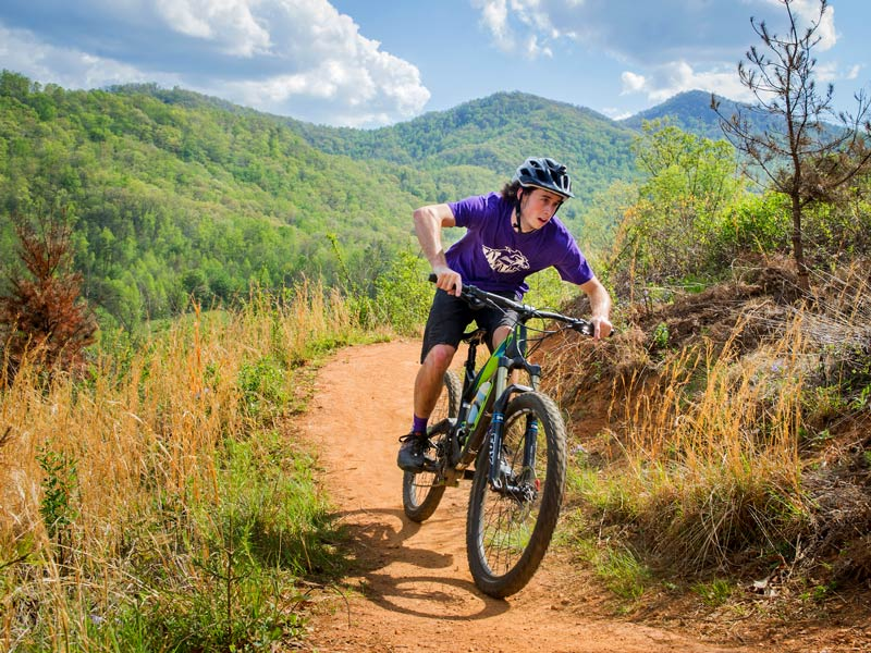 a male student rides his mountian bike on a dirt trail with mountians in the background