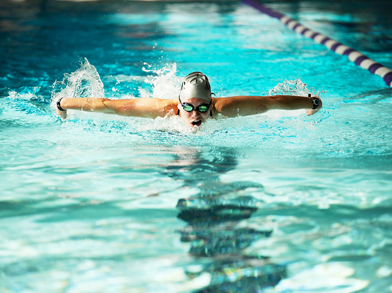 a person swimming laps in the campus swimming pool