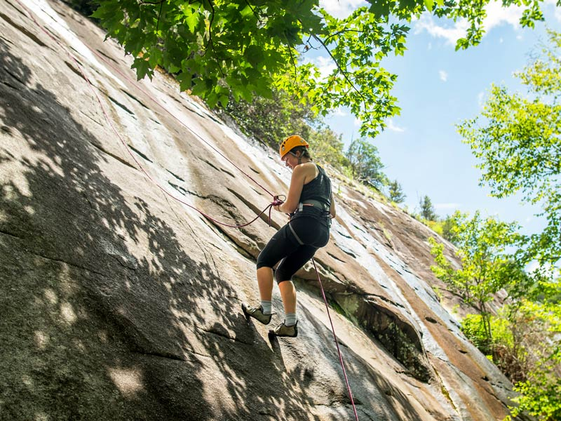 a student repels down a sloped rock face outdoors