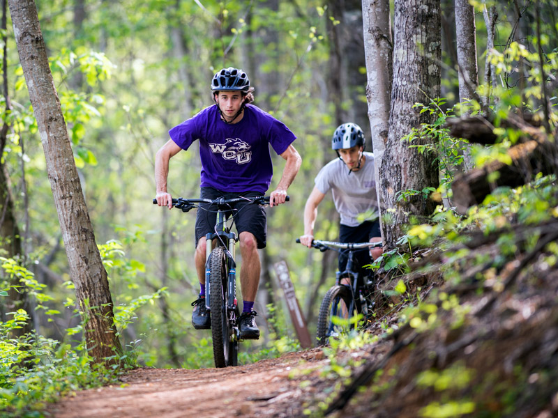 students riding bicycles on the campus trail