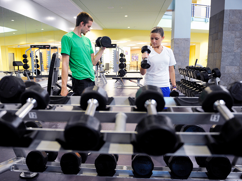 two students complete repetitions with arm weights in the weight room