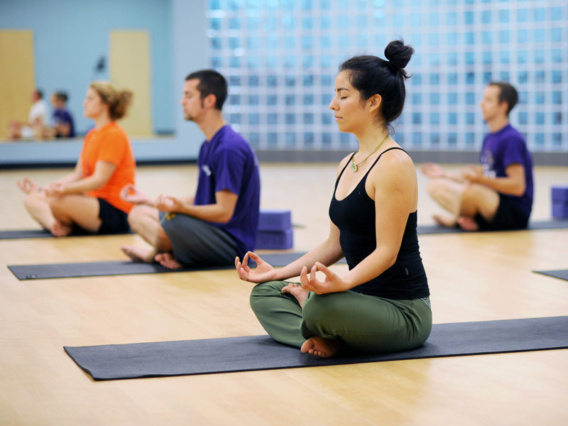 students participating in a yoga session on campus